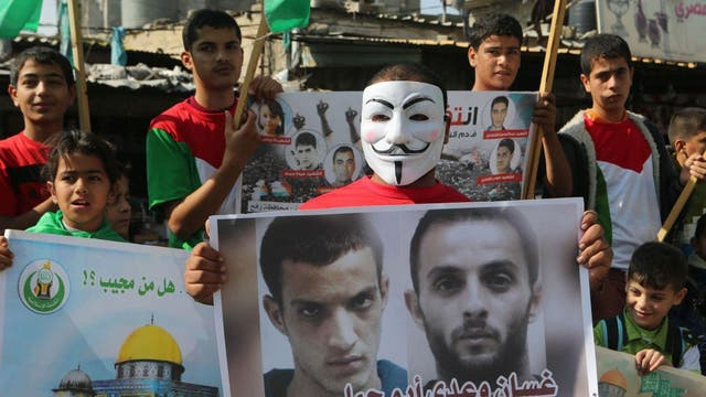 A masked Palestinian celebrates the attack on the Jerusalem synagogue holding a poster of the attackers,Ghassan and Uday Abu Jamal, during a rally in Rafah in the southern Gaza Strip