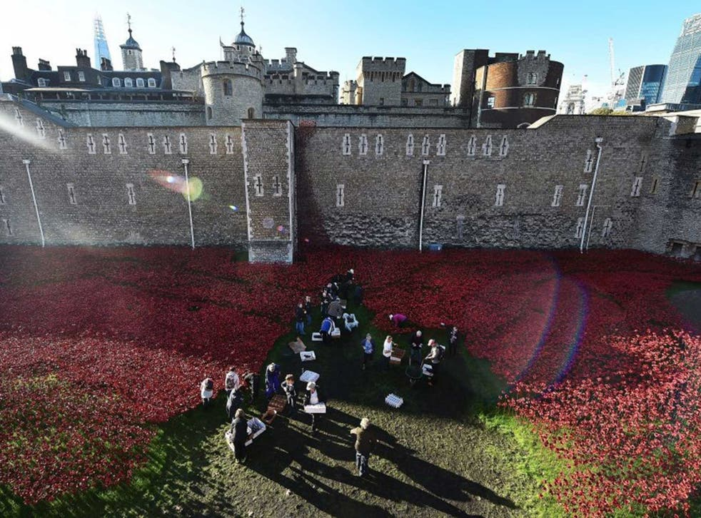 Volunteers start packing away the poppies surrounding the Tower of London