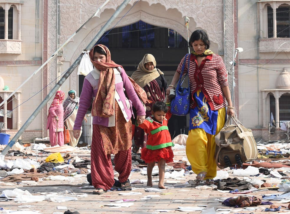 Followers leave the ashram of Sant Rampal in Hisar, India, where police discovered five bodies after storming the wanted guru's headquarters