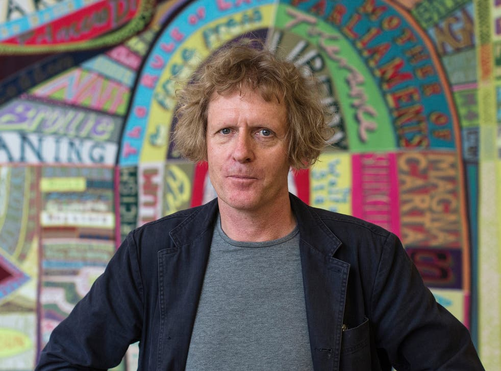 Artist Grayson Perry stands in front of a piece of his entitled 'Comfort Blanket' at the National Portrait gallery.