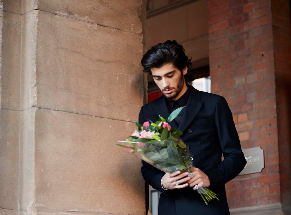 One Direction's Zayn Malik gazes at a bouquet of flowers in the 'Night Changes' music video