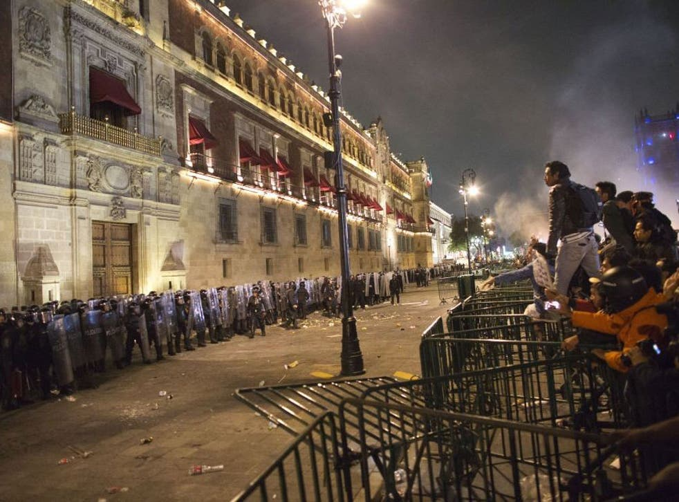 Protesters face federal police over barriers surrounding the National Palace in Mexico City, the latest in a wave of popular discontent to sweep the country