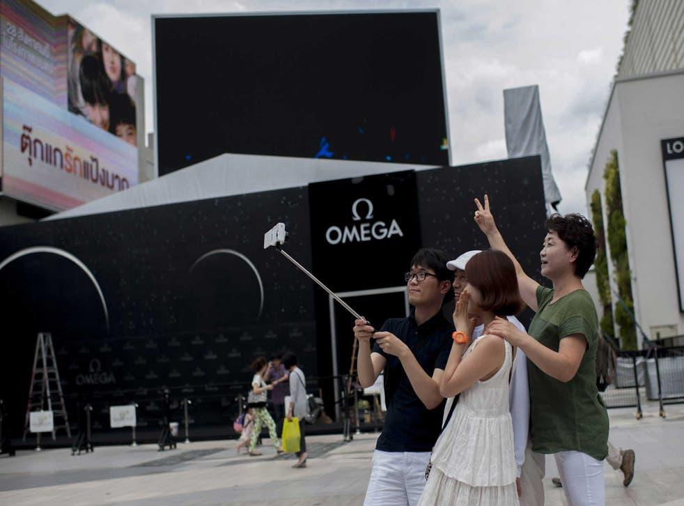 Tourists in Bangkok use a selfie stick