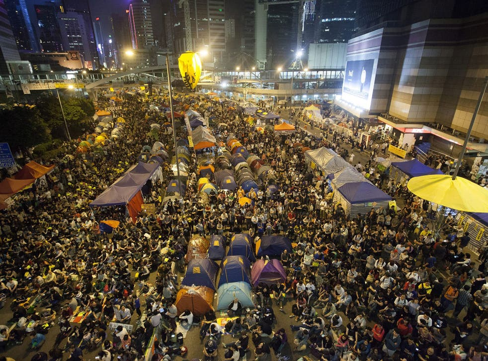 Pro-democracy student protesters in Hong Kong listen to speeches in the Occupy Central zone before clashing with police