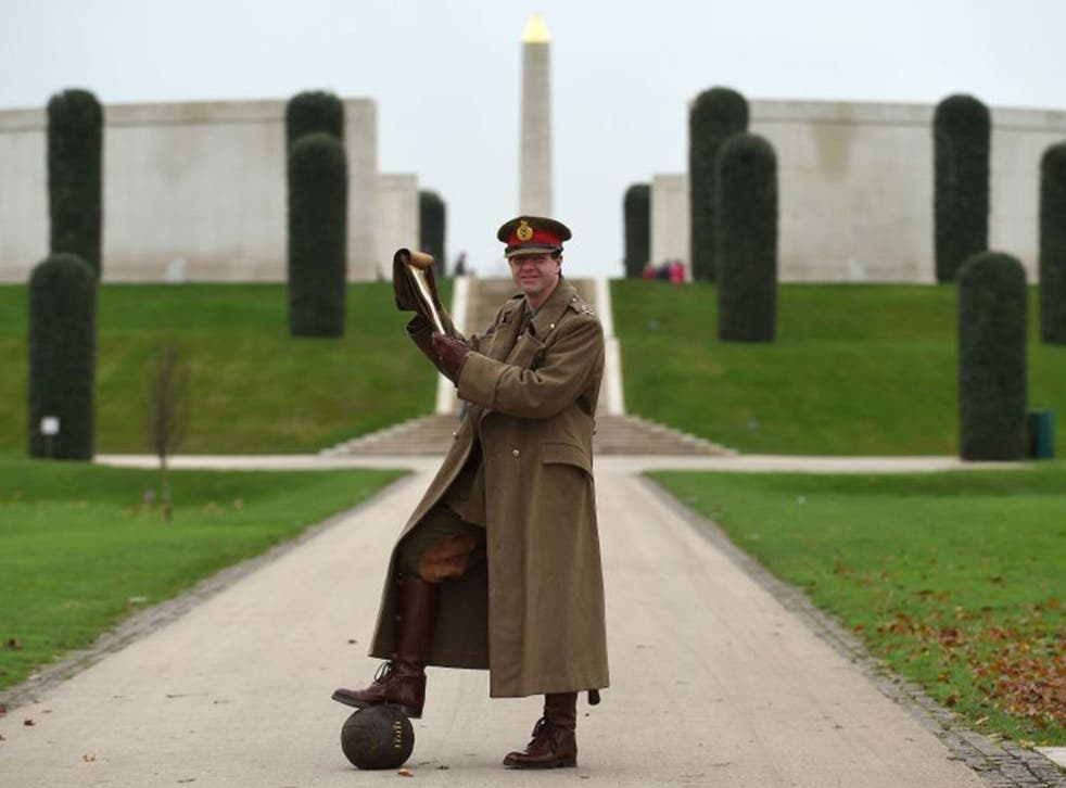 WW1 reenactor Paul Thompson, dressed in the uniform of a First World War General amongst the Shot at Dawn memorial at the National Memorial Arboretum in Alrewas, Staffordshire, reads a letter written by General Walter Congreve VC to his wife during the Fi