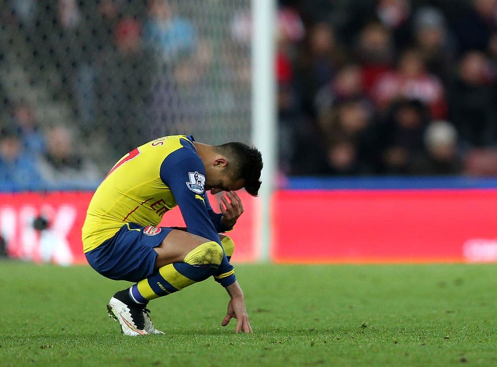 Alexis Sanchez holds his head after the 3-2 defeat to Stoke