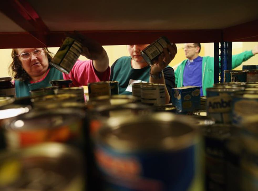 Volunteers assemble a selection of tinned food for a client at a food bank depot in Brixton, south London
