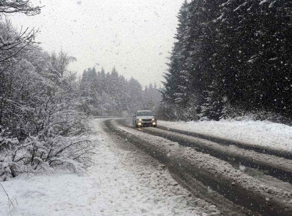 A car drives down the main road to Kielder in Northumberland, as snow continues to fall in the area.