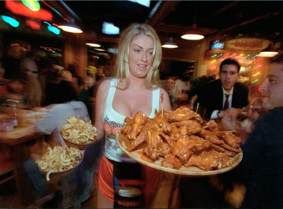 A waitress serves food to customers at Hooters