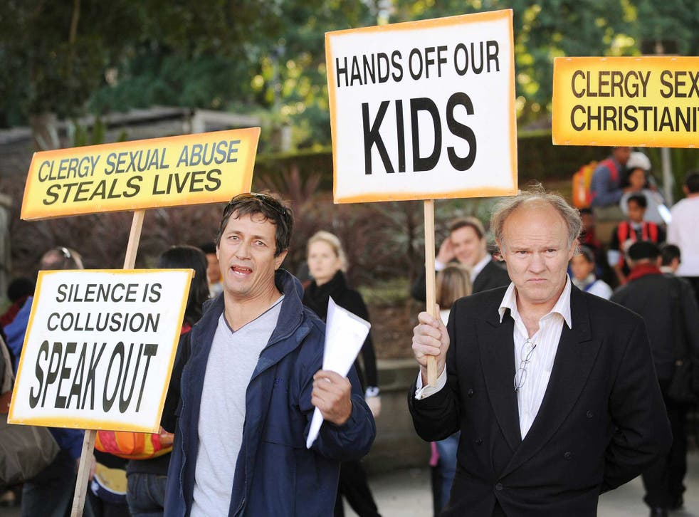 Activists protesting sexual abuse in the Catholic church hold up placards outside St Mary's Cathedral in Sydney