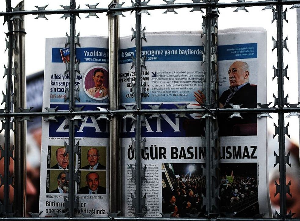 A supporter holds a copy of the Zaman newspaper behind a fence as police arrest its editor-in-chief in Istanbul.