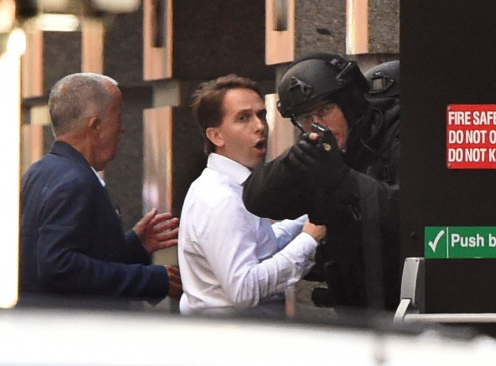 Two hostages run for cover behind a policeman during a hostage siege in a cafe in Sydney