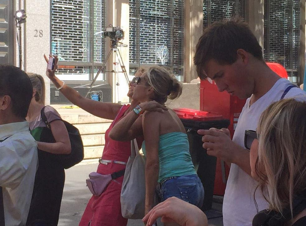Two women take a selfie photo close to the café where around 15 people were taken hostage