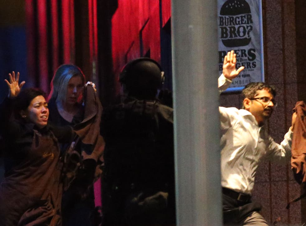 Hostages run towards armed tactical responce police as they run to freedom from a cafe under siege at Martin Place in the central business district of Sydney
