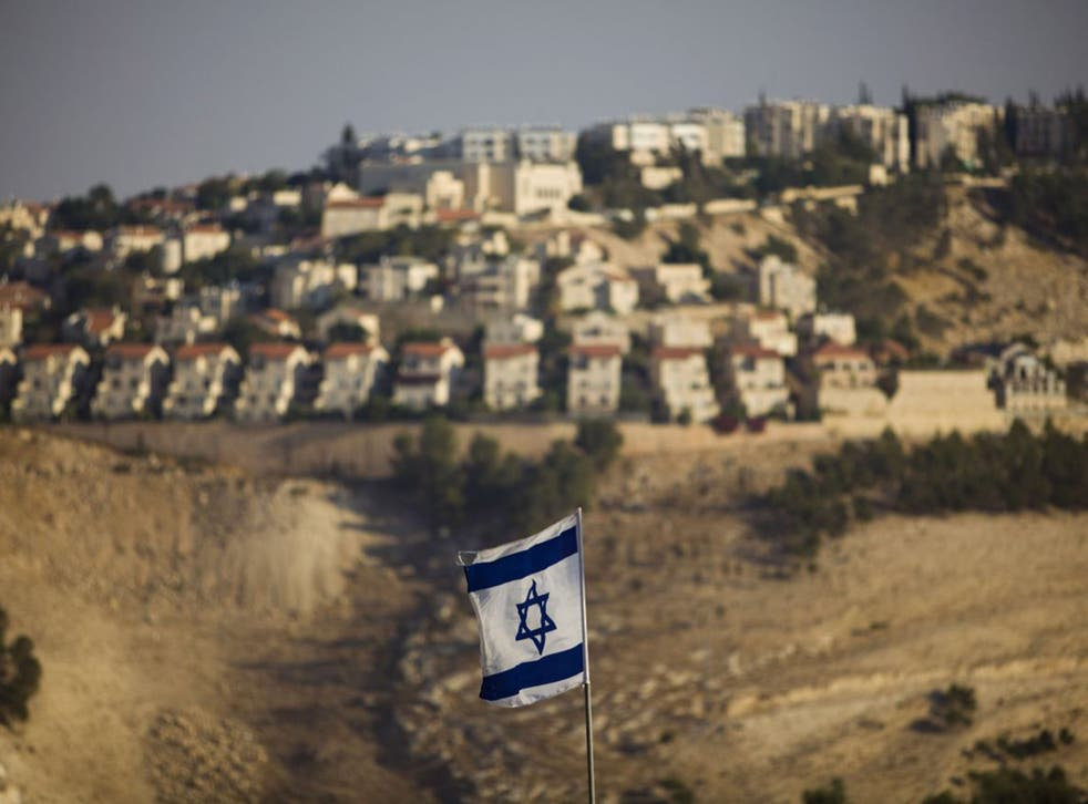 An Israeli flag flies in front of the West Bank Jewish settlement of Maaleh Adumim on the outskirts of Jerusalem in 2009 (AP)