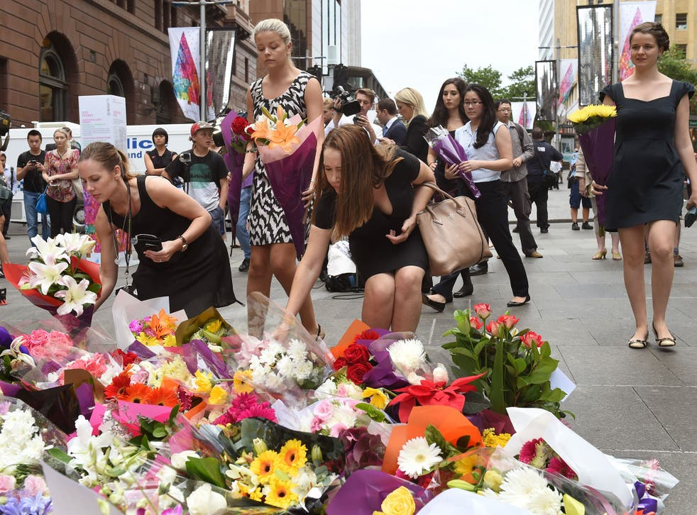 People lay flowers at a floral memorial at the scene of Sydney's siege