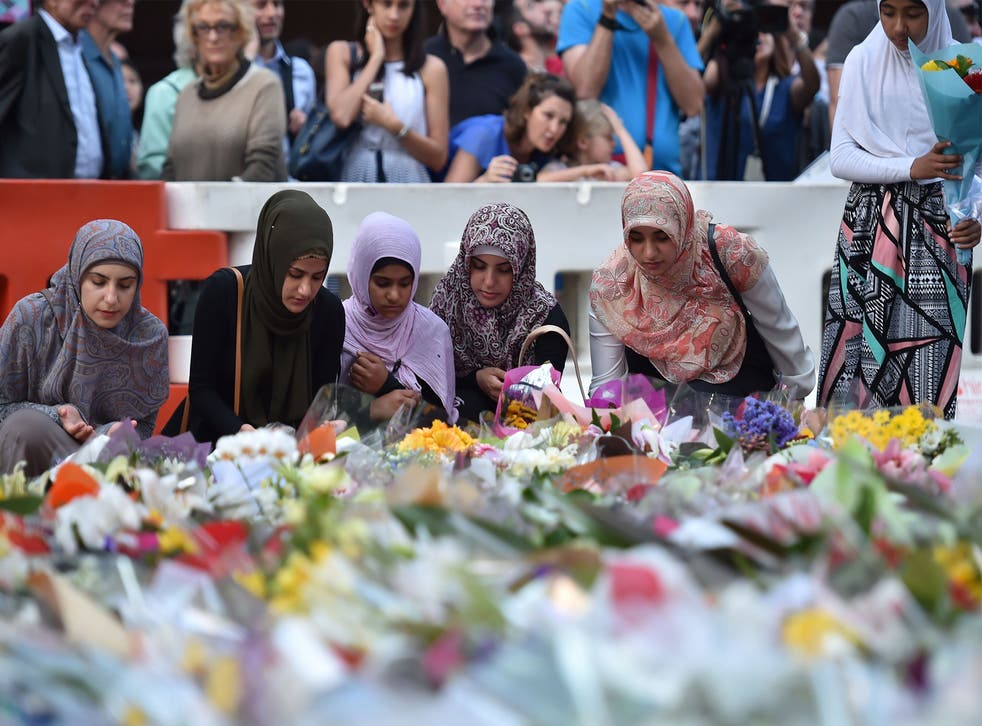 Young Muslim women lay flowers at a makeshift memorial near the scene of a fatal siege in the heart of Sydney's financial district on December 16, 2014.
