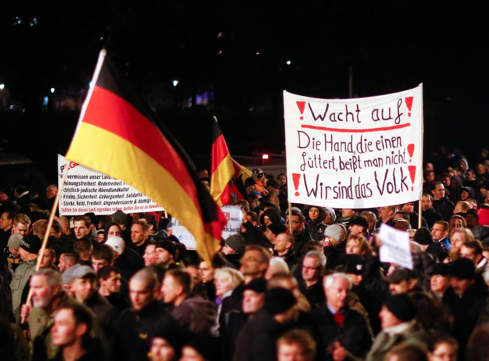 Participants hold German national flags and a banner during a demonstration called by anti-immigration group PEGIDA