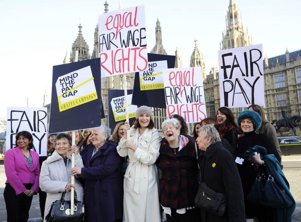 Gemma Arterton (C) holds a placard outside the Houses of Parliament to mark the tabling of the motion on equal pay earlier this year