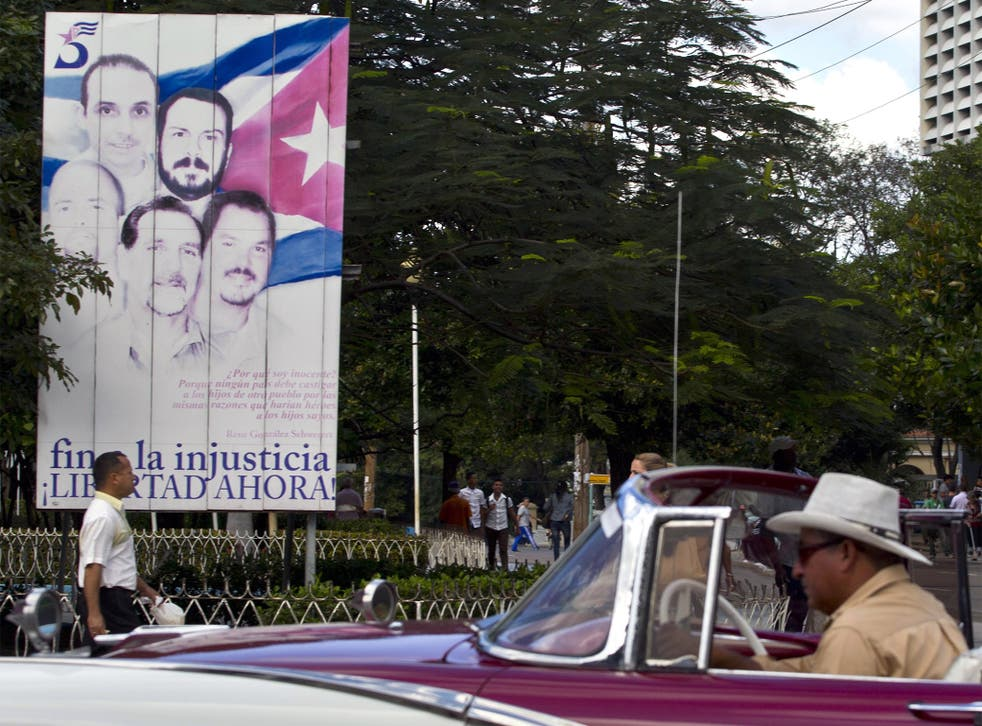 Tourists riding in a classic American car drive by a billboard showing 'The Cuban Five' that reads in Spanish 'End the injustice. Freedom now,' in Havana, Cuba