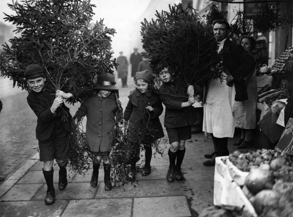 Children carry Christmas trees home in December 1923