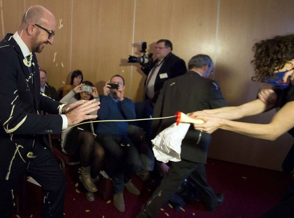 Belgian Prime Minister Charles Michel (L) reacts as activists throw fries and mayonnaise on him during an anti-government protest
