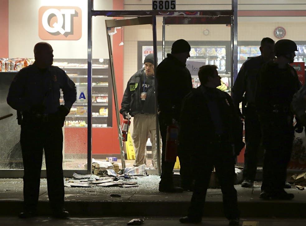 A police officer with a fire extinguisher stands in the broken out entry to a QuikTrip convenience store following the shooting