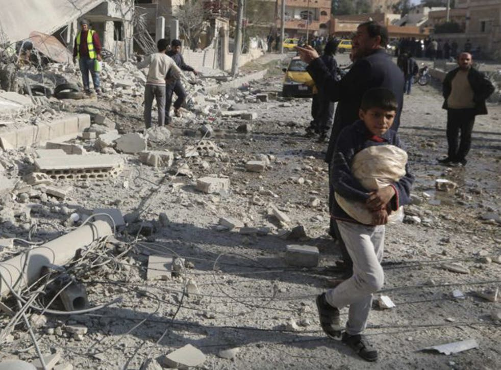 A boy carries bread as he walks past buildings in Raqqa destroyed by an air strike. Residents say water and electricity supplies are intermittent and food is running short