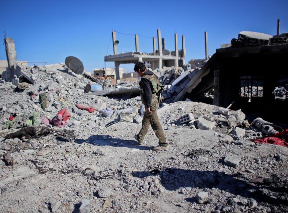 A Kurdish fighter walking past destroyed  homes in Kobani  Ahmed