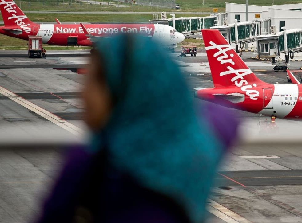 A Malaysian woman watches AirAsia Airbus A320 airplanes parked on the tarmac at the low-cost carrier Kuala Lumpur International Airport 2 (KLIA2) in Sepang on 28 December 2014