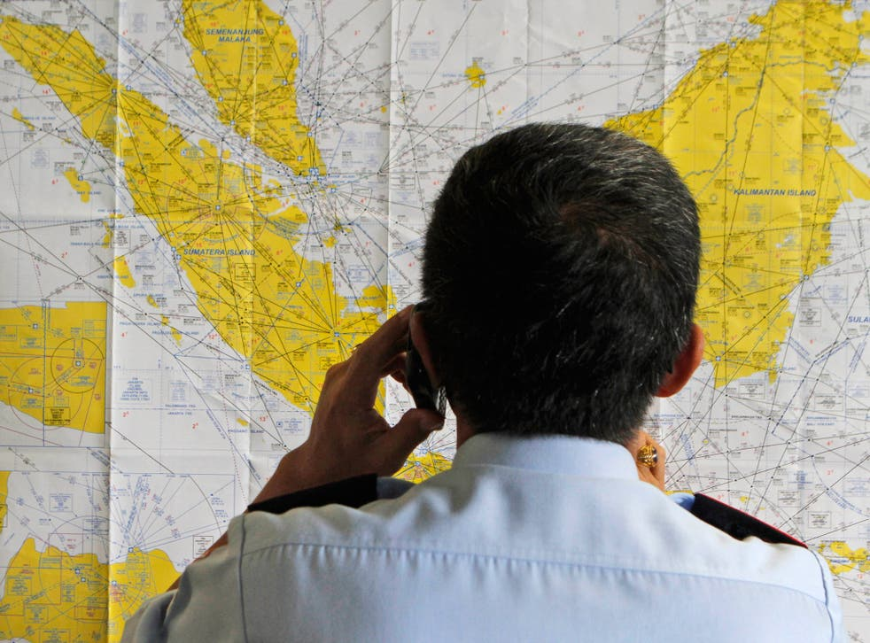 An airport official checks a map at the crisis centre set up by local authorities in the wake of AirAsia flight QZ8501 having gone missing