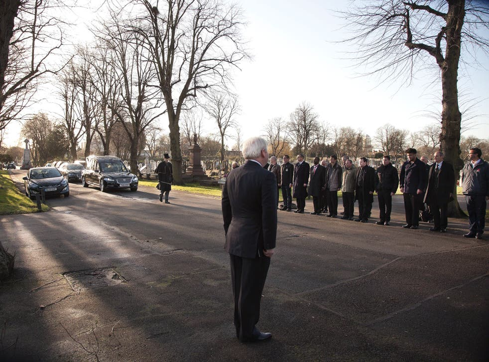 Mourners stand to attention to honour Ian Douglas