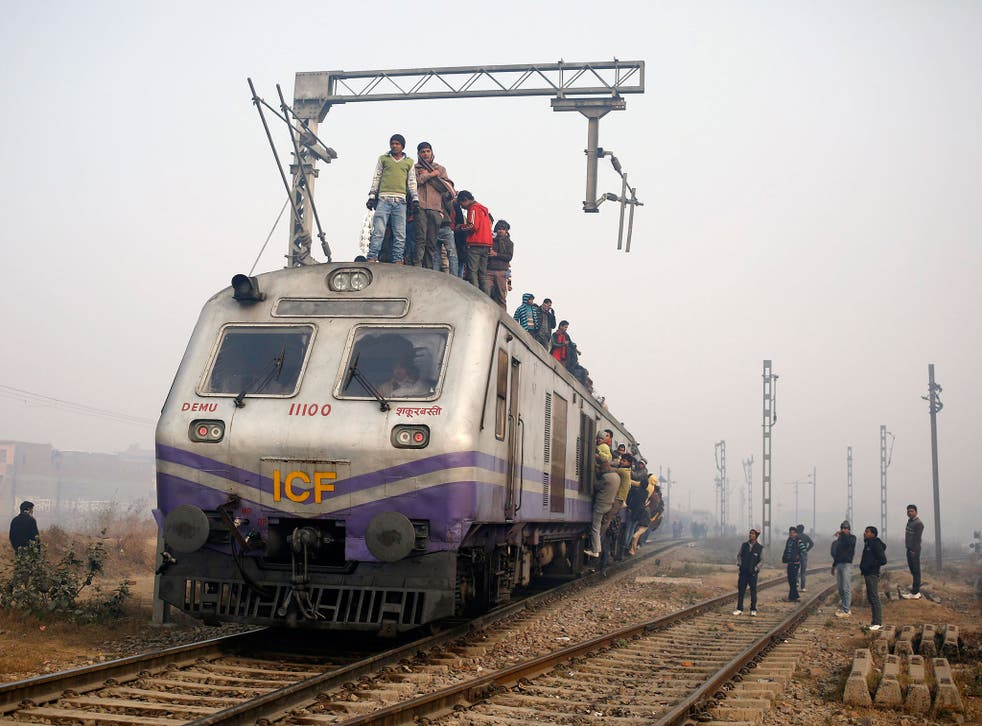 Passengers crowd atop a train as they travel on a cold winter morning at a railway station in Ghaziabad on the outskirts of New Delhi