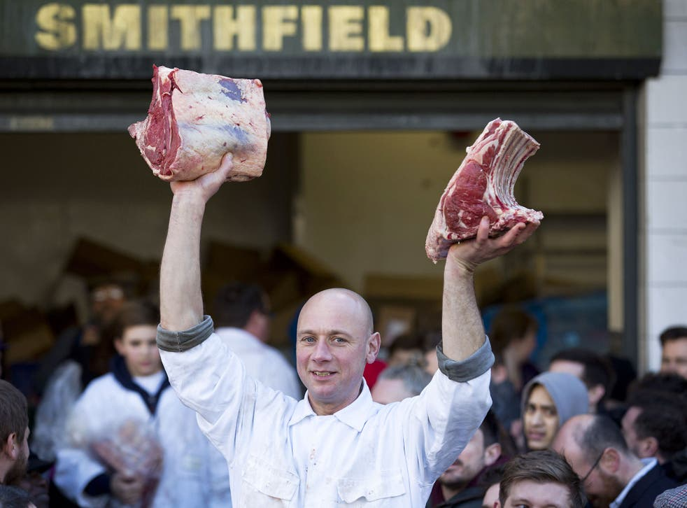 A butcher holds meat to sell during the annual Christmas Eve auction at Smithfield Market in central London