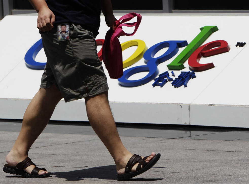 An employee walks past the logo of Google in front of its former headquarters, in Beijing June 2, 2011