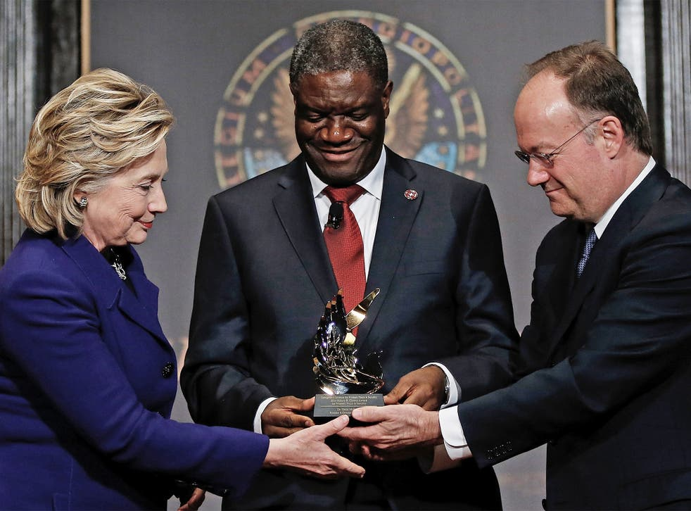 Force for good: Dr Denis Mukwege receives a humanitarian award from Hillary Clinton and Georgetown University head, John De Gioia
