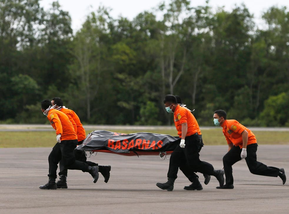 Search and rescue team members carry the dead body of a passenger onboard AirAsia flight QZ8501 in Indonesia