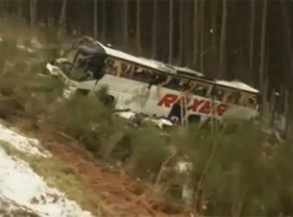 The bus lies by the side of the road after the crash