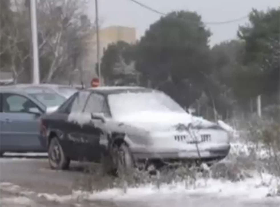 A car is coated in snow as Greece experiences a spell of severe winter weather