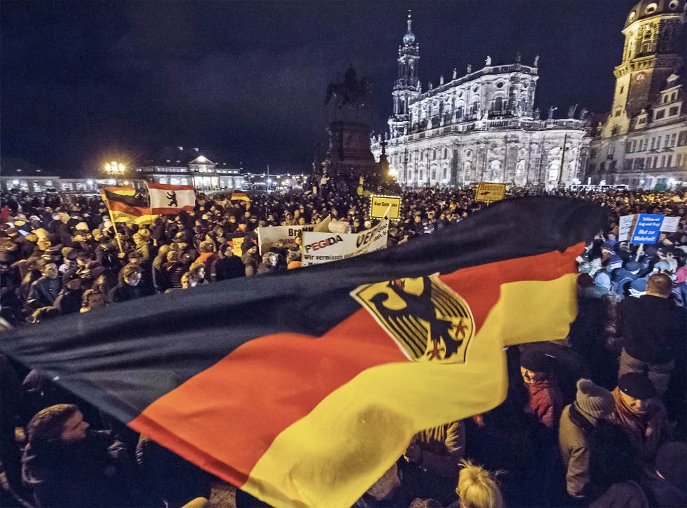 Supporters at a Pegida rally hold German flags and lights during a demonstration held each week for the past 10 weeks in front of the Dresden Cathedral in eastern Germany