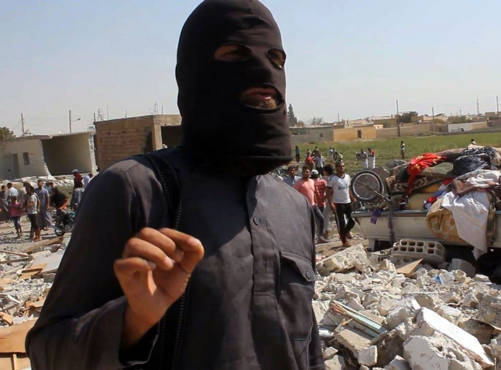 An Isis jihadist pictured standing on the rubble of houses after a Syrian warplane was reportedly shot down by Isis militants over the Syrian town of Raqa in September, 2014