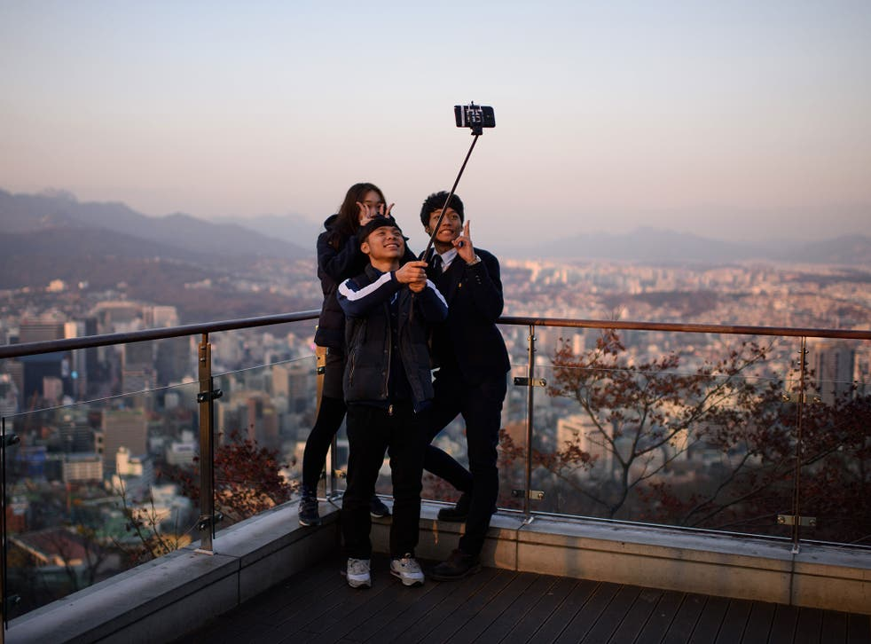 People use a 'selfie stick' to take a group photo overlooking the city skyline of Seoul