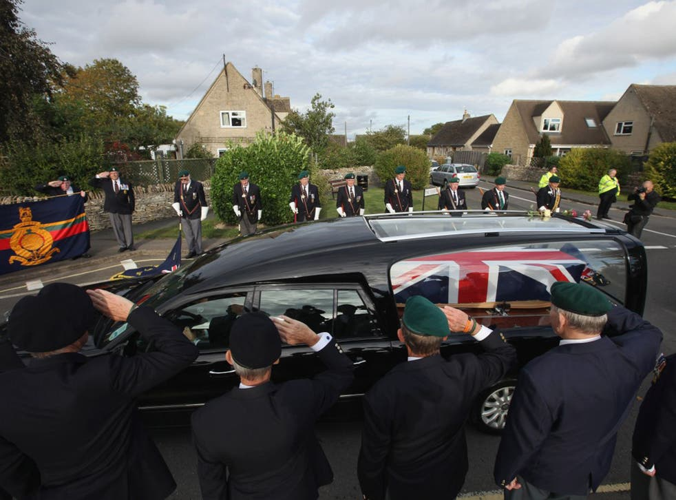 Retired Royal Marine personnel salute as a hearse passes through the village of Brize Norton in 2011 (Getty)