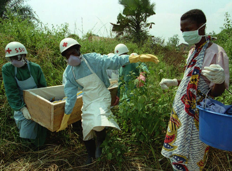 A woman walks beside the body of her mother during the 1995 Kikwit Ebola outbreak in what was then Zaire