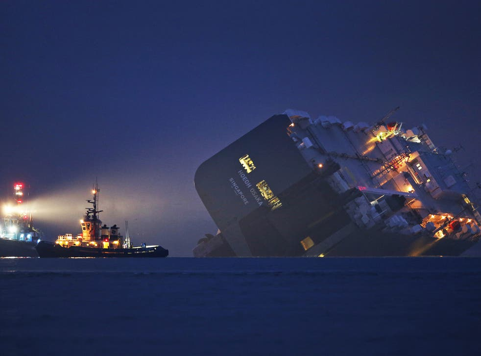 A salvage tug lights the hull of the stricken Hoegh Osaka cargo ship after it ran aground on a sand bank in the Solent in Cowes. The cargo ship ran aground on Bramble Bank after leaving Southampton bound for Germany. All 25 crew members were rescued overn