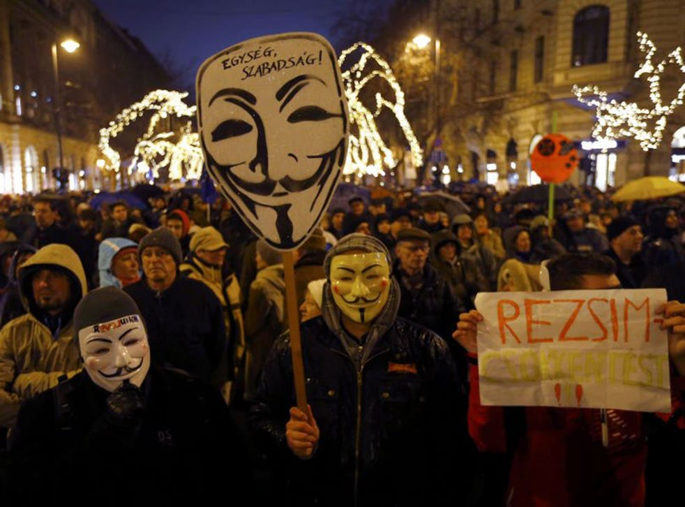 Anti-government protesters wear Guy Fawkes masks and hold a placard reading 'regime' in Budapest  last week (Reuters)
