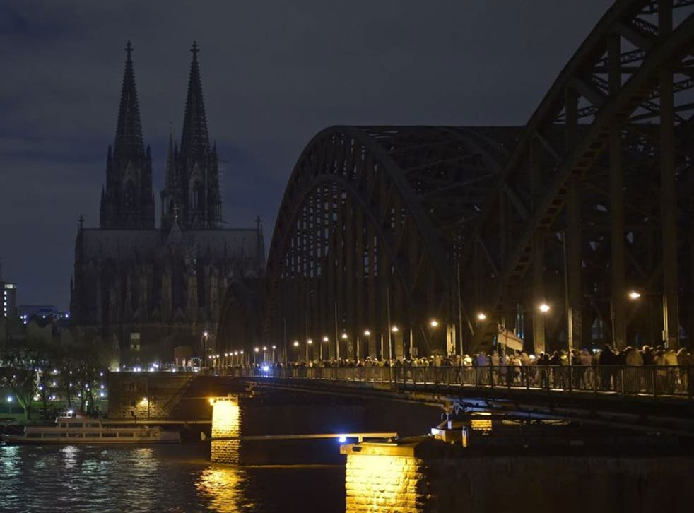 Anti-Pegida protesters march across a bridge in Cologne as the cathedral goes dark in support on 5 January