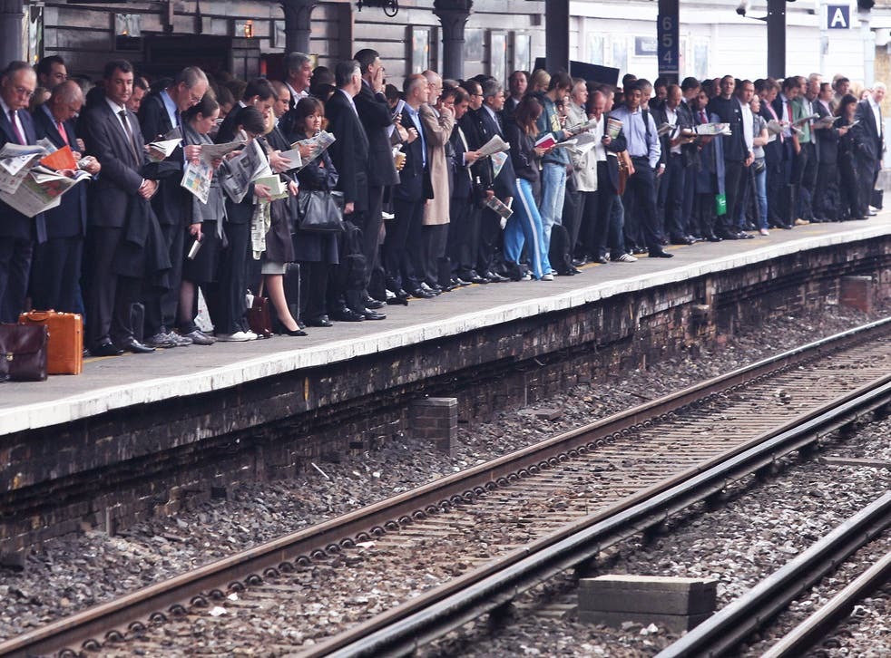 Commuters wait for their train