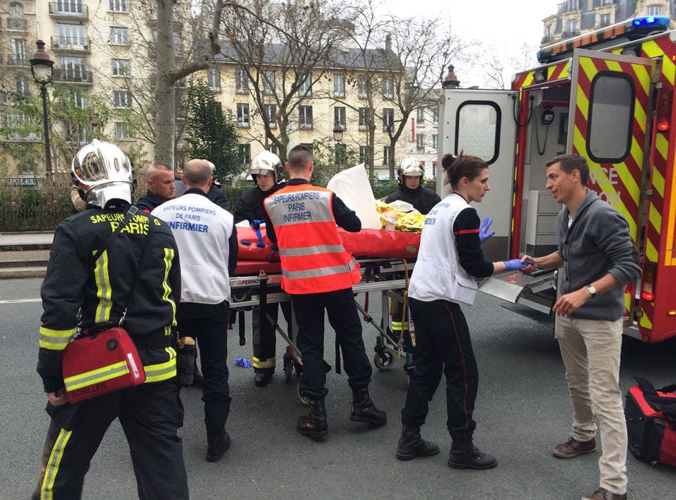 Firefighters carry an injured man on a stretcher in front of the offices of the French satirical newspaper Charlie Hebdo in Paris