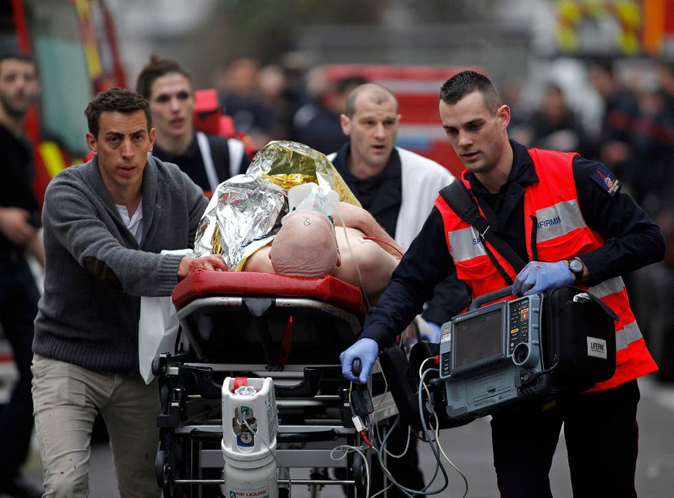 An injured person is evacuated outside the French satirical newspaper Charlie Hebdo's office in Paris